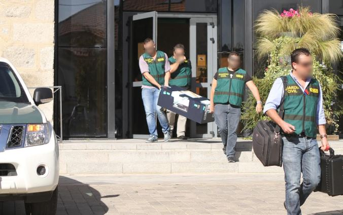 Agentes de la Guardia Civil saliendo con documentación del Ayuntamiento de Collado Villalba